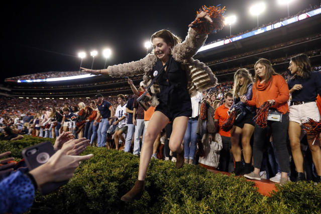Some Auburn fans had better luck than others storming the field after an upset win over No. 5 Alabama at the Iron Bowl. (AP Photo/Butch Dill)