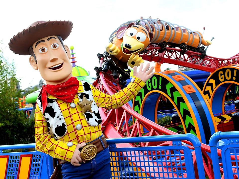 """Woody from """"Toy Story"""" stands in front of Slinky Dog Dash at Disney World in 2018."""
