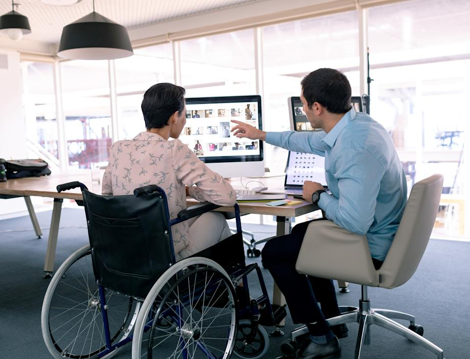 Rear view of diverse graphic designers discussing over computer at desk in a modern office. Disabled mixed-race female designer is sitting in wheelchair.