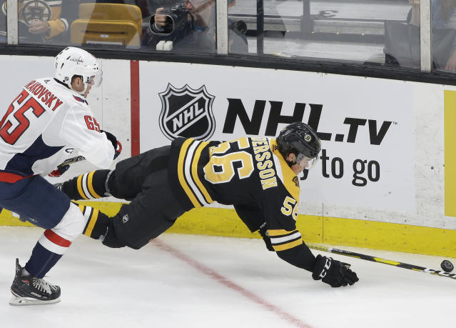 Washington Capitals' Andre Burakovsky, of Austria, left, and Boston Bruins' Axel Andersson, of Sweden, right, vie for control of the puck in the second period of an NHL preseason hockey game, Sunday, Sept. 16, 2018, in Boston. The Bruins won 2-1 in a shootout. (AP Photo/Steven Senne)