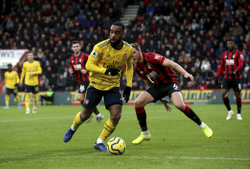 Arsenal's Alexandre Lacazette, front, takes the ball from Bournemouth's Dan Gosling during their English Premier League soccer match at the Vitality Stadium, Bournemouth, England, Thursday, Dec. 26, 2019. (Mark Kerton/PA via AP)