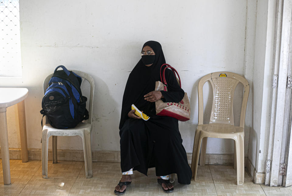 A woman waits to test for COVID-19 during a random test for the family members of army personnel at the army base hospital in Gauhati, India, Monday, Oct. 19, 2020. (AP Photo/Anupam Nath)