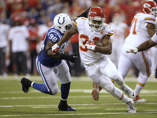 Kansas City Chiefs running back Knile Davis (34) runs from Indianapolis Colts outside linebacker Robert Mathis (98) during the first half of an NFL wild-card playoff football game Saturday, Jan. 4, 2014, in Indianapolis. (AP Photo/AJ Mast)