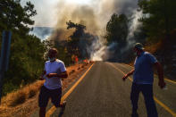 People run away as the wildfires engulf an area near the seashore, forcing people to be evacuated by boats, in Bodrum, Mugla, Turkey, Sunday, Aug. 1, 2021. Wildfires in the Turkish holiday destinations of Antalya and Mugla are still raging as firefighters worked to battle the blazes for a fifth day. Authorities warned tourists and residents to keep evacuating Turunc, a town in the seaside resort of Marmaris, and navy ships waited in the sea there to see if a bigger evacuation was needed. (Ismail Coskun/IHA via AP)