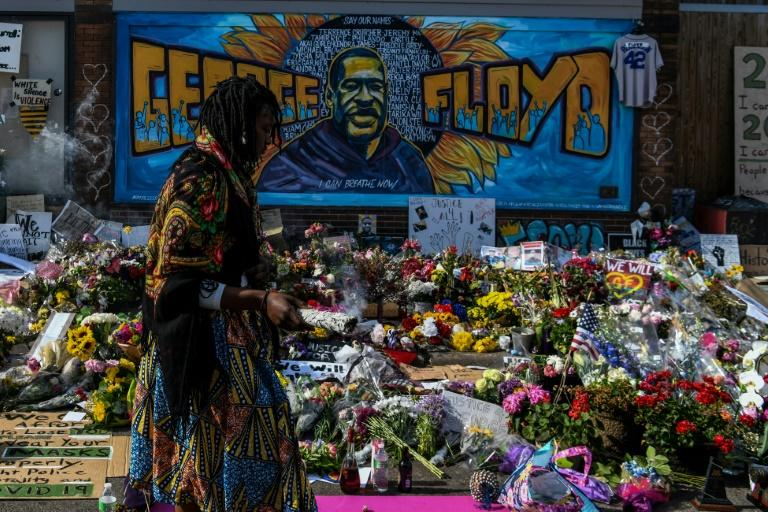A woman burns sage and offers prayers as she pays her respects at a makeshift memorial in honor of George Floyd, who died while in police custody on May 25