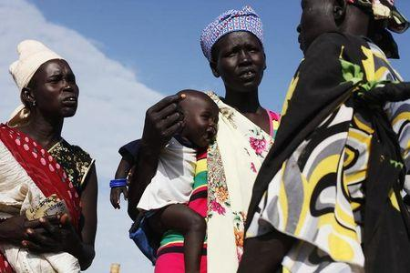 A woman carries a baby as she talks with other women talk at a food distribution in Minkaman
