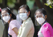 Participants wearing protective face mask and shield stand as they take part in a demonstration of the voting for upcoming Nov.8 general election, Tuesday, Oct. 20, 2020, in Naypyitaw, Myanmar. (AP Photo/Aung Shine Oo)