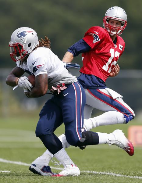 New England Patriots quarterback Tom Brady (12) hands off to New England Patriots running back Brandon Bolden during NFL football practice in Foxborough, Mass., Monday, Aug. 19, 2013. (AP Photo/Michael Dwyer)