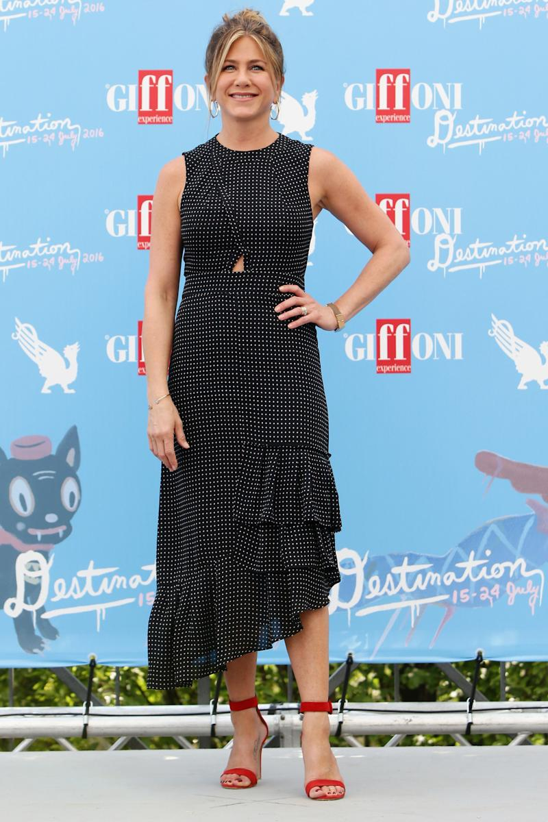 Jennifer Aniston wearing a black and white dress with red shoes on the red carpet at Italy's Giffoni Film Festival. (Photo: Getty Images)