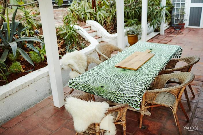 <p>The dining table on our back patio, where we eat every day. The tablecloth is just yardage of African fabric I brought back from a store in Paris. The chairs are from Ikea! A little lambskin will make anything more cozy.</p>