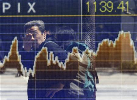 A man is reflected on a screen displaying a graph showing movements of the Tokyo Stock Exchange Stock Price Index (TOPIX), outside a brokerage in Tokyo April 14, 2014. REUTERS/Issei Kato