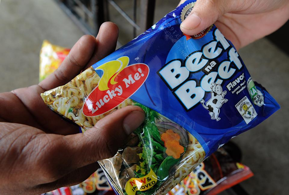 FILE PHOTO: This photo illustration shows a man buying instant noodles made by local instant noodle firm Monde Nissin at a village convenience store in suburban Manila on October 11, 2015.  (Photo: JAY DIRECTO/AFP via Getty Images)
