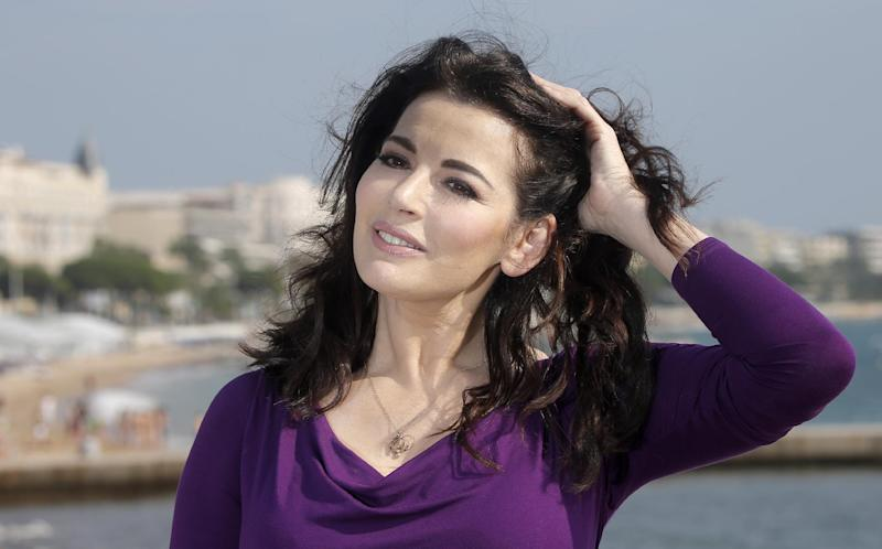 FILE - In this Tuesday, Oct. 9, 2012 file photo, food writer, journalist and broadcaster, Nigella Lawson of Britain poses during the 28th International Film and Programme Market for TV, Video, Cable and Satellite in Cannes, southeastern France. In summer 2013, photos of her husband appearing to choke her surfaced. Then two former employees accused of using the couple's credit cards for more than $1 million in fraudulent charges claiming she had sanctioned their spending to hush them up about her heavy drug use. (AP Photo/Lionel Cironneau, File)