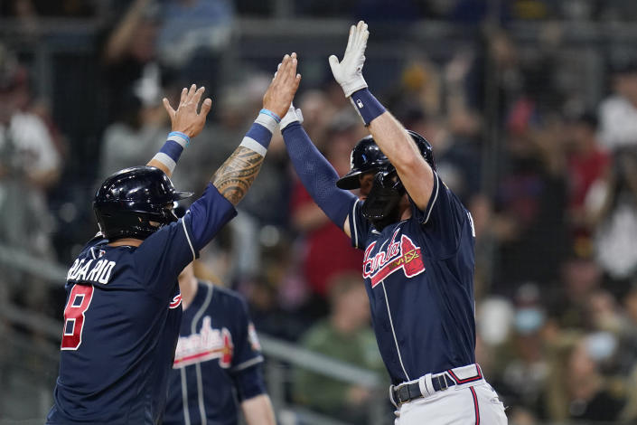Atlanta Braves' Dansby Swanson, right, reacts with teammate Eddie Rosario after hitting a two-run home run during the second inning of a baseball game against the San Diego Padres, Friday, Sept. 24, 2021, in San Diego. (AP Photo/Gregory Bull)