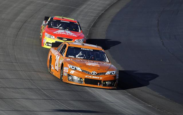 Matt Kenseth, front, competes against Jeff Gordon, back, during a NASCAR Sprint Cup series auto race, on