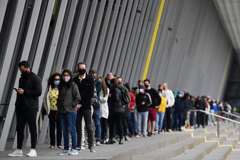 People are seen waiting in a line at a Covid19 vaccination centre in Melbourne on Friday. Source: AAP