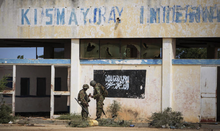 In this photo released by the African Union-United Nations Information Support Team, Kenyan soldiers serving with the African Union Mission in Somalia (AMISOM) stand in front of the black flag of al-Shabab painted on a wall at the airport in Kismayo, southern Somalia, Tuesday, Oct. 2, 2012. Allied African troops have taken full control of Kismayo in Somalia, the last stronghold of al-Shabab Islamist rebels who have been fighting against the country's internationally backed government, a Kenyan military official said Tuesday, and Kenya Defence Forces and the Somali National Army are now patrolling the streets. (AP Photo/AU-UN IST, Stuart Price)