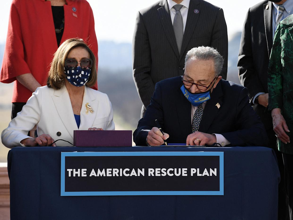 Speaker of the House Nancy Pelosi (L) and Senate Majority Leader Chuck Schumer sign the American Rescue Plan Act after the House Chamber voted on the final revised legislation of the $1.9 trillion Covid-19 relief plan, at the US Capitol on March 10, 2021 in Washington, DC. - The US Congress on Wednesday passed Joe Biden's enormous economic relief package, delivering a resounding victory for the US president and a desperately needed injection of cash to millions of families and businesses enduring the coronavirus pandemic. (Photo by OLIVIER DOULIERY / AFP) (Photo by OLIVIER DOULIERY/AFP via Getty Images)