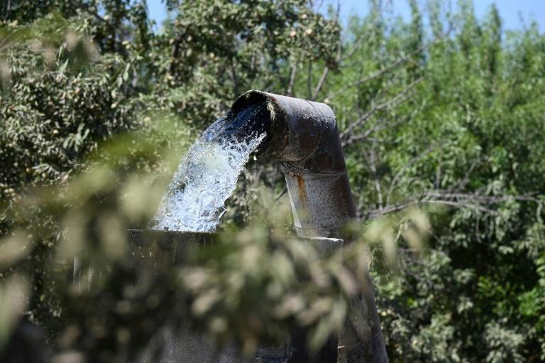 Water pumped up from an underground well flows into a cistern on a farm in Fresno, California