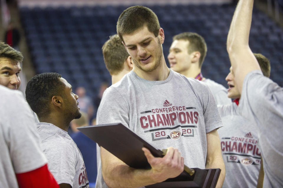 FILE - Belmont's Seth Adelsperger (50) smiles as he look down at the tournament championship trophy after an NCAA college basketball game against Murray State for the championship of the Ohio Valley Conference men's tournament in Evansville, Ind., in this Saturday, March 7, 2020, file photo. Belmont is joining the Missouri Valley Conference on July 1 and leaving the Ohio Valley Conference after nine years. (AP Photo/Daniel R. Patmore)