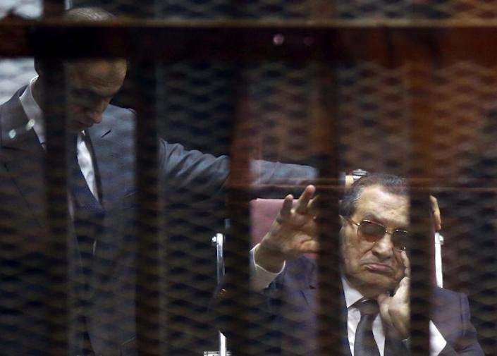 Ousted Egyptian president Hosni Mubarak (R) waves from the defendant's cage next to one of his sons, Gamal, in their retrial for embezzlement on May 9, 2015 in Cairo (AFP Photo/Mostafa el-Shemy)
