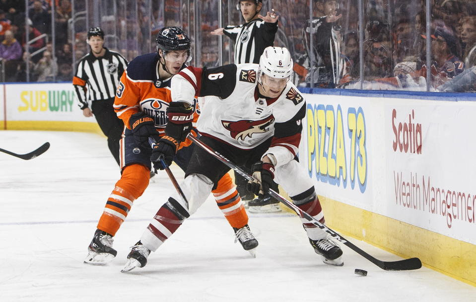 Arizona Coyotes' Jakob Chychrun (6) and Edmonton Oilers' Ryan Nugent-Hopkins (93) battle for the puck during first period NHL action in Edmonton, Alberta, on Saturday Jan. 18, 2020. (Jason Franson/The Canadian Press via AP)