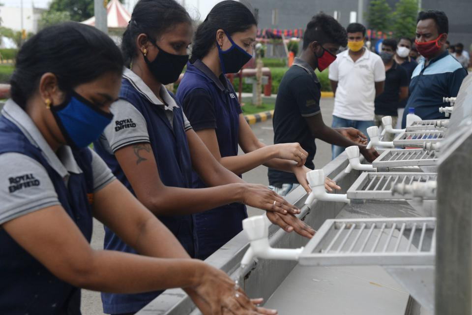 This picture taken on June 9, 2020 shows workers washing their hands upon their arrival at the Royal Enfield motorcycle factory after the government eased a nationwide lockdown imposed as a preventive measure against the COVID-19 coronavirus, in Oragadam, Tami Nadu. (Photo by Arun SANKAR / AFP) (Photo by ARUN SANKAR/AFP via Getty Images)