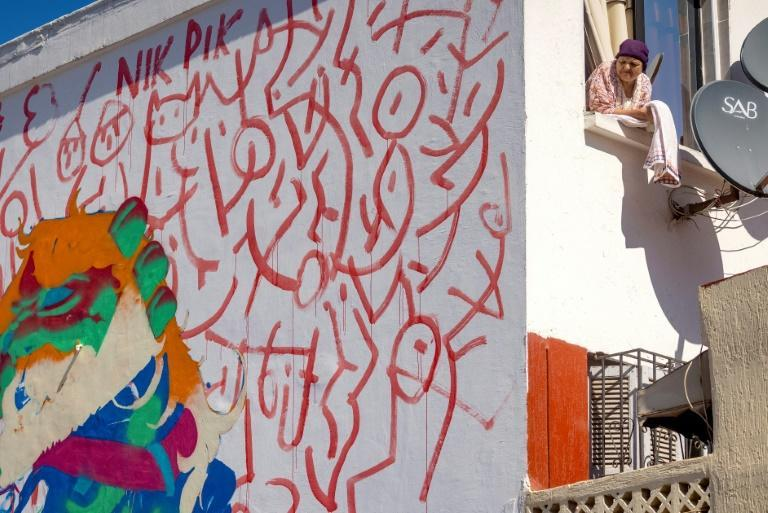 A woman looks on from her window next to a mural by Moroccan street artist Omar Lhamzi (AFP/FADEL SENNA)