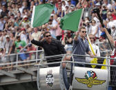 FILE - In this May 26, 2019, file photo, actors Christian Bale, left, and Matt Damon wave green flags to start Indianapolis 500 IndyCar auto race at Indianapolis Motor Speedway in Indianapolis. The Indianapolis 500 scheduled for May 24 has been postponed until August because of the coronavirus pandemic and won't run on Memorial Day weekend for the first time since 1946. The race will instead be held Aug. 23. (AP Photo/Michael Conroy)