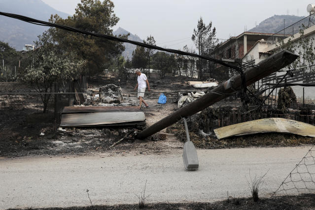 <p>A man collects belongings after a forest fire in Kineta village, west of Athens, Tuesday, July 24, 2018. (Photo: Yorgos Karahalis/AP) </p>