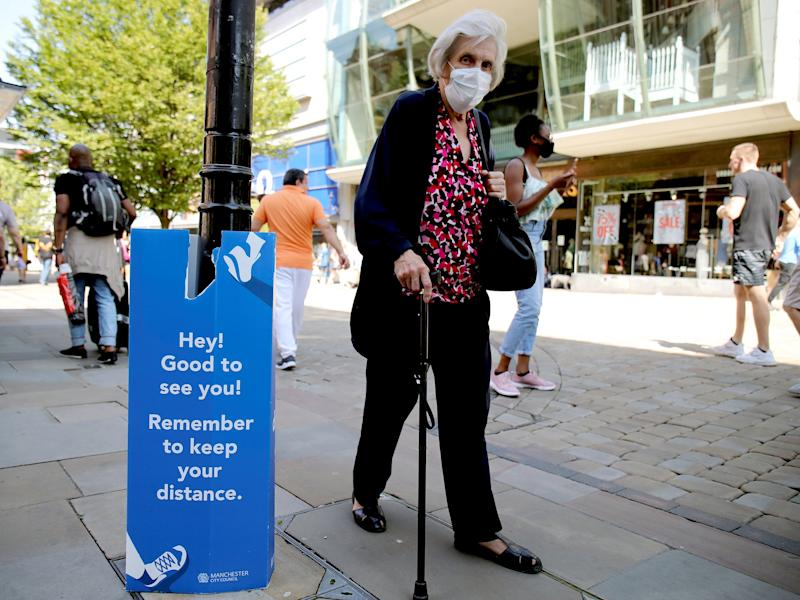 A woman wearing a protective mask walks down the street in Manchester as the city and surrounding areas face local restrictions amid a coronavirus outbreak: Reuters