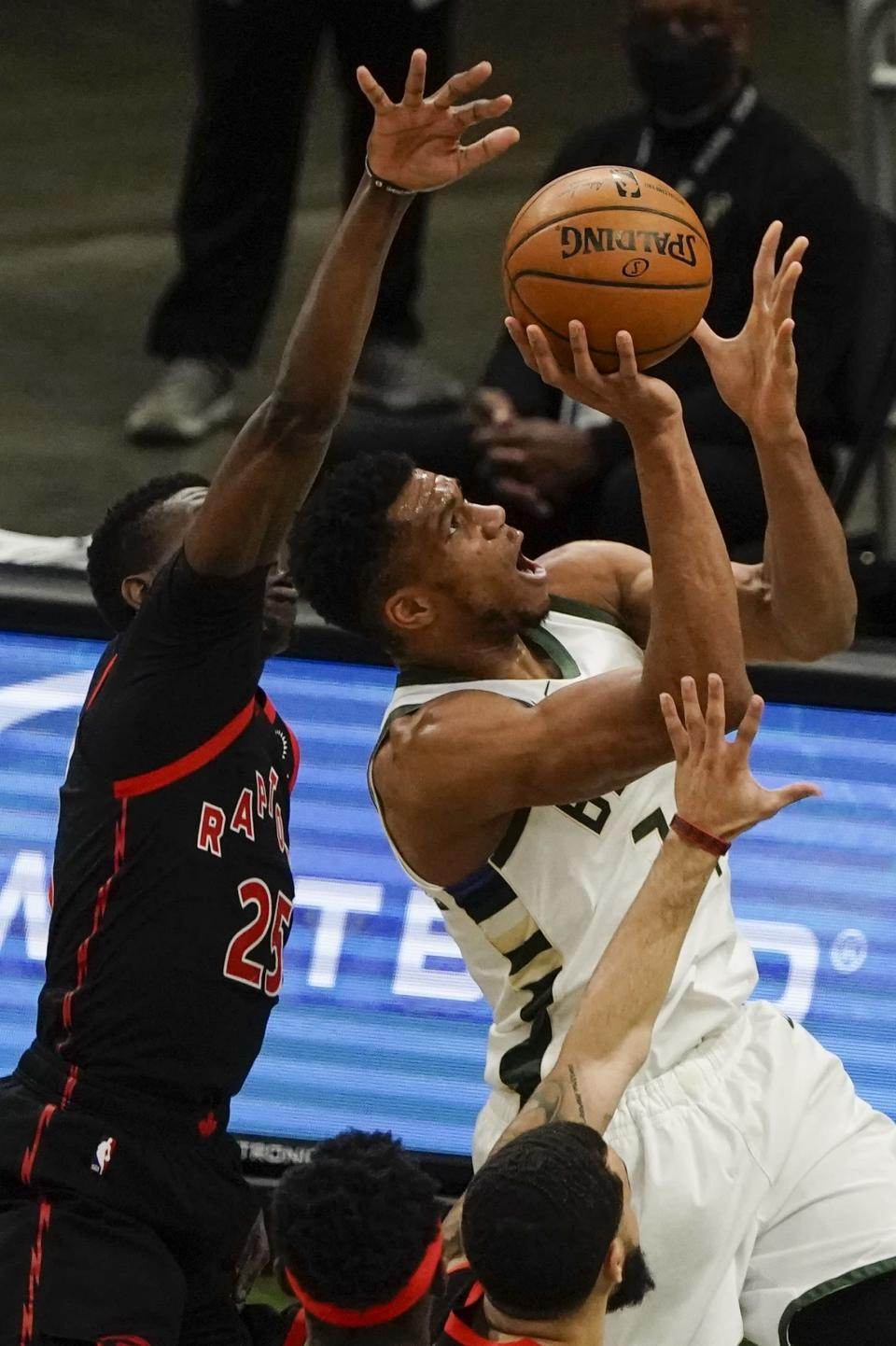 Milwaukee Bucks' Giannis Antetokounmpo shoots past Toronto Raptors' Chris Boucher during the first half of an NBA basketball game Tuesday, Feb. 16, 2021, in Milwaukee. (AP Photo/Morry Gash)