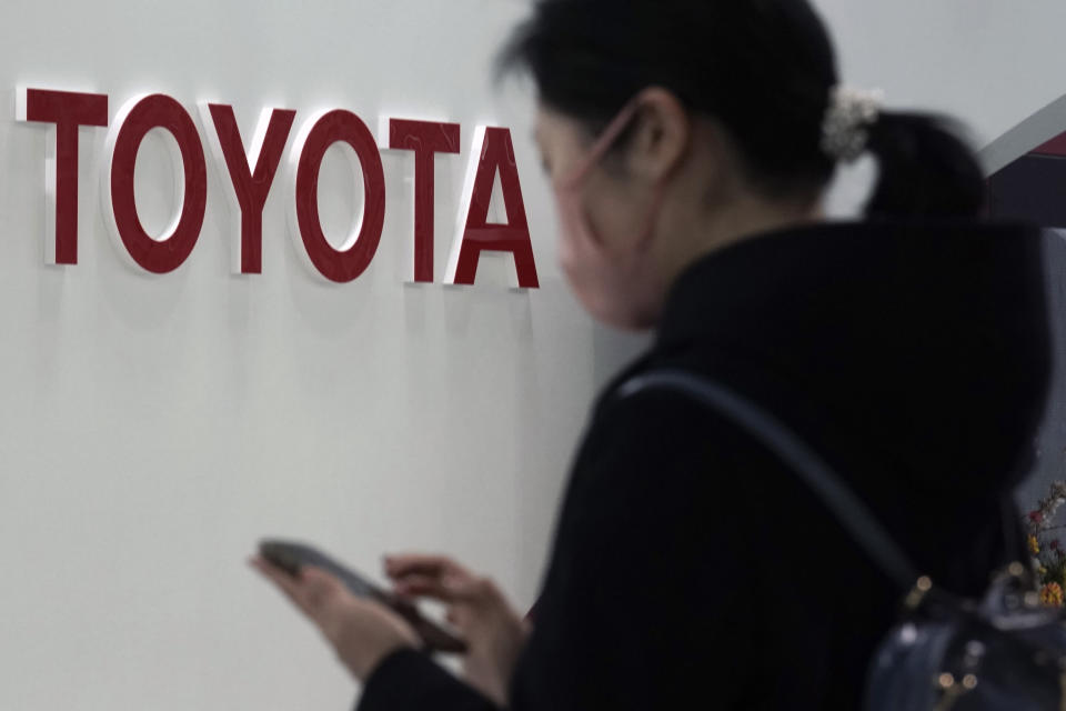 FILE - In this Jan. 30, 2020, file photo, a visitor stands by the logo of Toyota Motor Corp. at its showroom in Tokyo. Toyota's April-June profit plunged 74% as the coronavirus pandemic crushed vehicle sales to about half of what the top Japanese automaker sold the previous year, reported Thursday, Aug. 6, 2020. (AP Photo/Eugene Hoshiko, File)