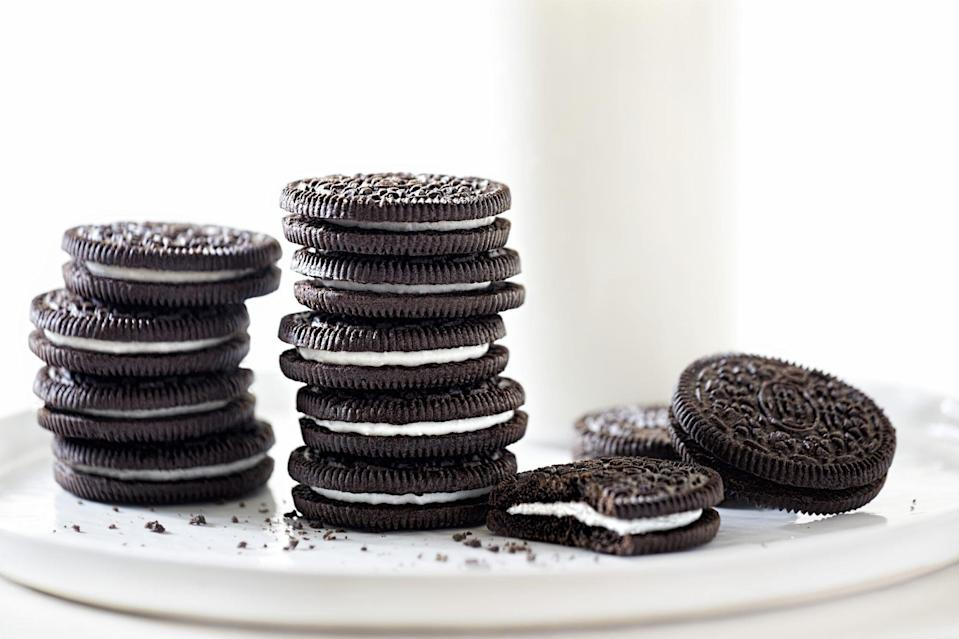 Oreo cookies stacked with milk on white background