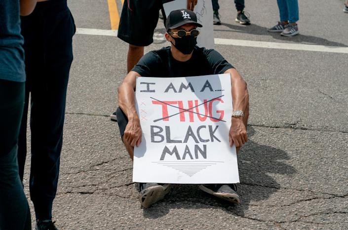 <i>A seated protester holds a sign during a June 2 demonstration in Los Angeles over the death of George Floyd.</i>