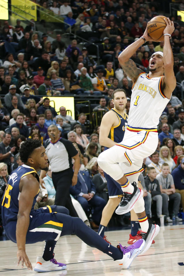 Utah Jazz guard Donovan Mitchell (45) falls as Golden State Warriors guard Damion Lee (1) shoots in the first half during an NBA basketball Friday, Dec. 13, 2019, in Salt Lake City. (AP Photo/Rick Bowmer)