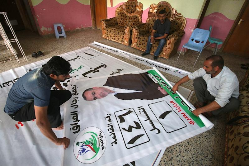 Supporters of candidate for the upcoming Iraqi parliamentary elections Abdel Amir Najem work on a campaign poster that will hang in Basra (AFP Photo/HAIDAR MOHAMMED ALI, HAIDAR MOHAMMED ALI)