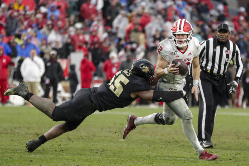 Indiana quarterback Peyton Ramsey (12) tries to scramble away from Purdue defensive end Derrick Barnes (55) during the second half of an NCAA college football game in West Lafayette, Ind., Saturday, Nov. 30, 2019. Indiana defeated Purdue 44-41 in double overtime. (AP Photo/Michael Conroy)