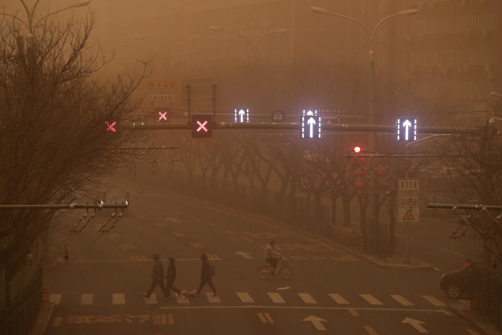 People walk across a street as capital city is hit by polluted air and sandstorm in Beijing, Monday, March 15, 2021. The sandstorm brought a tinted haze to Beijing's skies and sent air quality indices soaring on Monday. (AP Photo/Andy Wong)