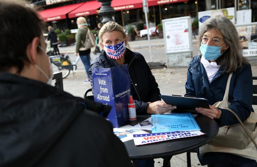 BERLIN, GERMANY - OCTOBER 10: Renee Johnsson of Democrats Abroad (C) and Florian Schiedhelm of Vote from Abroad (L) assist U.S. citizen Emily Schalk to register to vote absentee in the U.S. presidential elections to be held on November 3, at a Starbucks coffeeshop on October 10, 2020 in Berlin, Germany. Approximately 2.9 million Americans are eligible to vote from abroad, according to estimates from the Federal Voting Assistance Program. (Photo by Adam Berry/Getty Images)