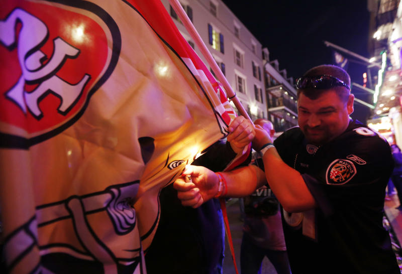Baltimore Ravens fan Mike Libber, burns a San Francisco 49ers flag while partying on Bourbon Street in downtown New Orleans, as revelers gather in the city's French Quarter, Friday, Feb. 1, 2013. The city kicked off NFL football Super Bowl weekend as it awaits for Sunday's game between the San Francisco 49ers and the Baltimore Ravens at the Superdome. (AP Photo/Julio Cortez)