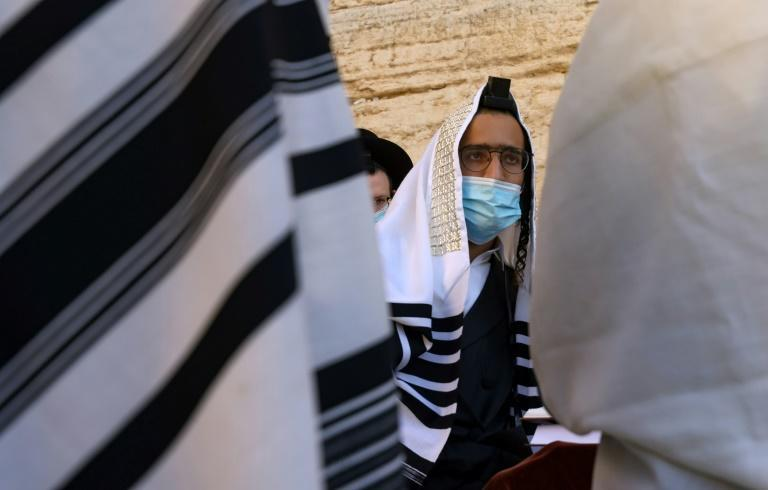 A young Ultra-Orthodox Jewish man wears a facemask and a tefillin during prayers at the Western Wall in the Old City of Jerusalem in this file picture taken on October 18, 2020 amid the coronavirus pandemic