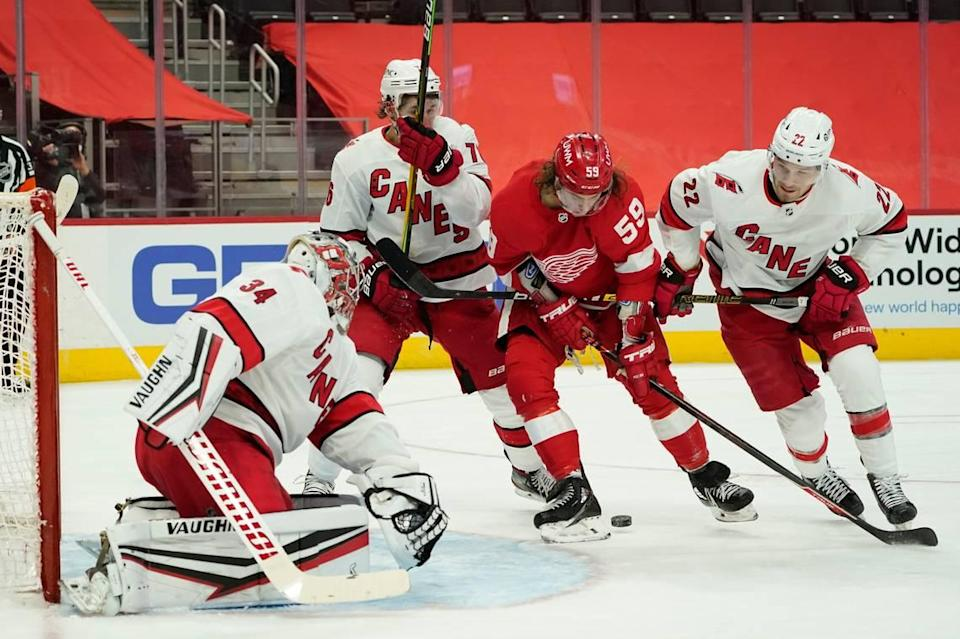 Detroit Red Wings left wing Tyler Bertuzzi (59) tries to get a shot on Carolina Hurricanes goaltender Petr Mrazek (34) in the second period of an NHL hockey game Thursday, Jan. 14, 2021, in Detroit. (AP Photo/Paul Sancya)