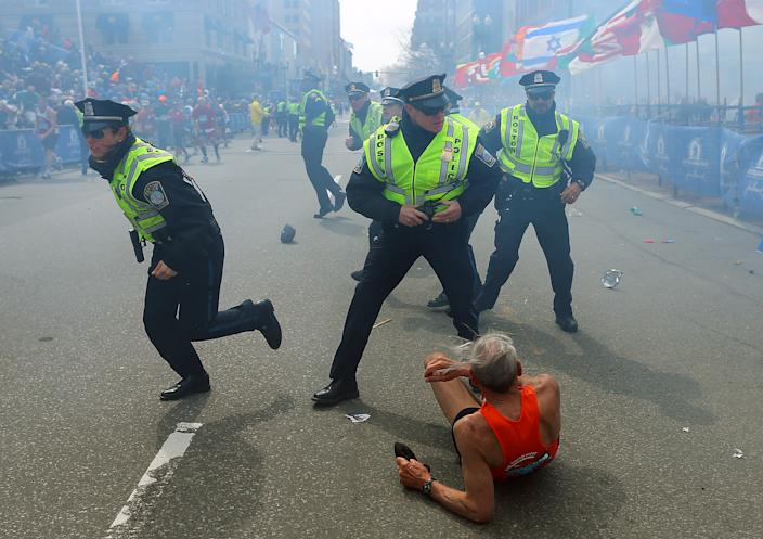 Police officers with their guns drawn hear the second explosion down the street t the Boston Marathon. The first explosion knocked down 78-year-old US marathon runner Bill Iffrig at the finish line of the 117th Boston Marathon. (John Tlumacki/The Boston Globe via Getty Images)