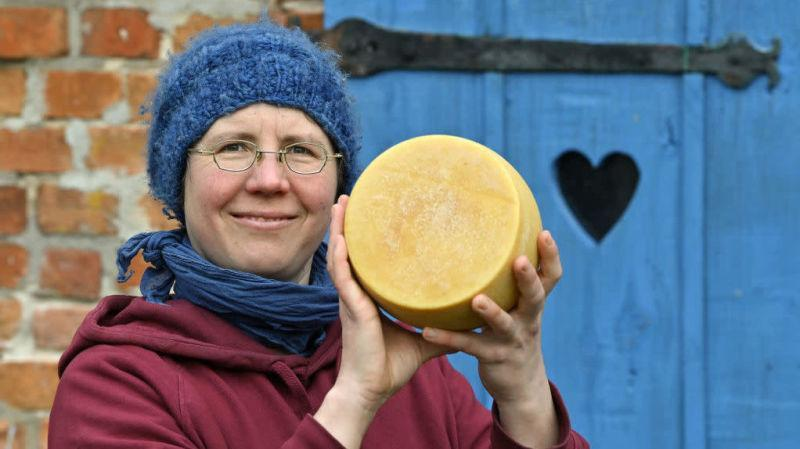 woman proudly holding cheese