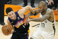 Phoenix Suns guard Devin Booker, left, is defended by Milwaukee Bucks forward P.J. Tucker during the first half of Game 5 of basketball's NBA Finals, Saturday, July 17, 2021, in Phoenix. (AP Photo/Matt York)