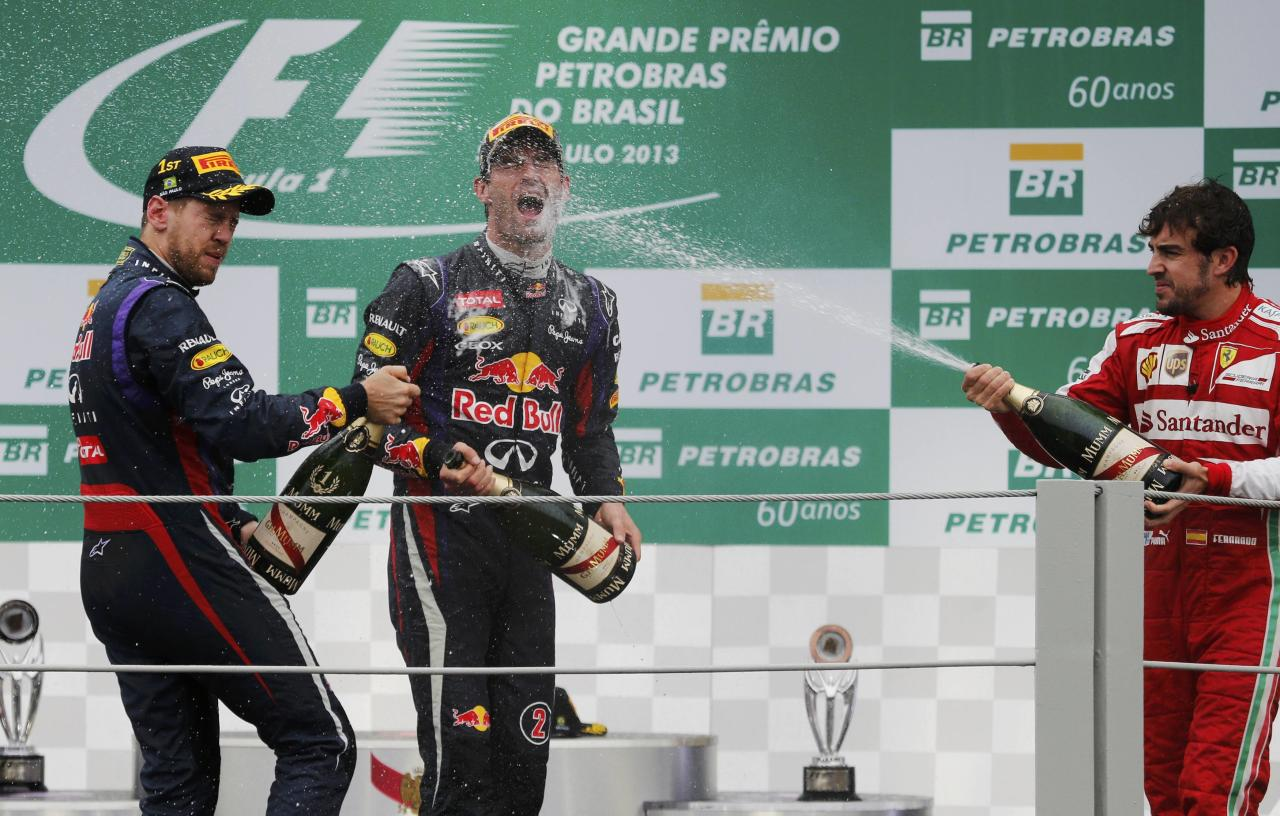 Red Bull Formula One driver Sebastian Vettel (L-R) of Germany, teammate Mark Webber of Australia and Ferrari Formula One driver Fernando Alonso of Spain spray champagne as they celebrate on the podium after the Brazilian F1 Grand Prix at the Interlagos circuit in Sao Paulo November 24, 2013. REUTERS/Nacho Doce (BRAZIL - Tags: SPORT MOTORSPORT F1 TPX IMAGES OF THE DAY)