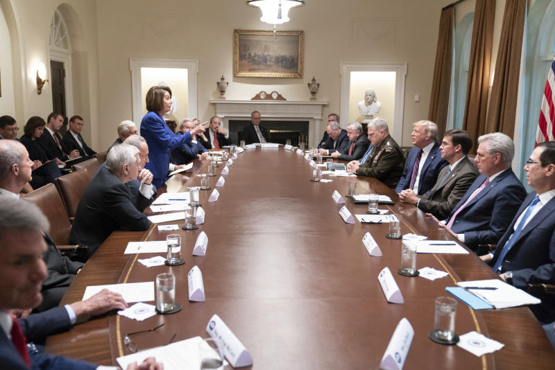 In this photo released by the White House, President Donald Trump, center right, meets with House Speaker Nancy Pelosi, standing left, Congressional leadership and others, Wednesday, Oct. 16, 2019, in the Cabinet Room of the White House in Washington. Trump and Pelosi have not spoken in five months at a time when the nation is battling its worst health crisis in a century. (Official White House Photo by Shealah Craighead via AP)