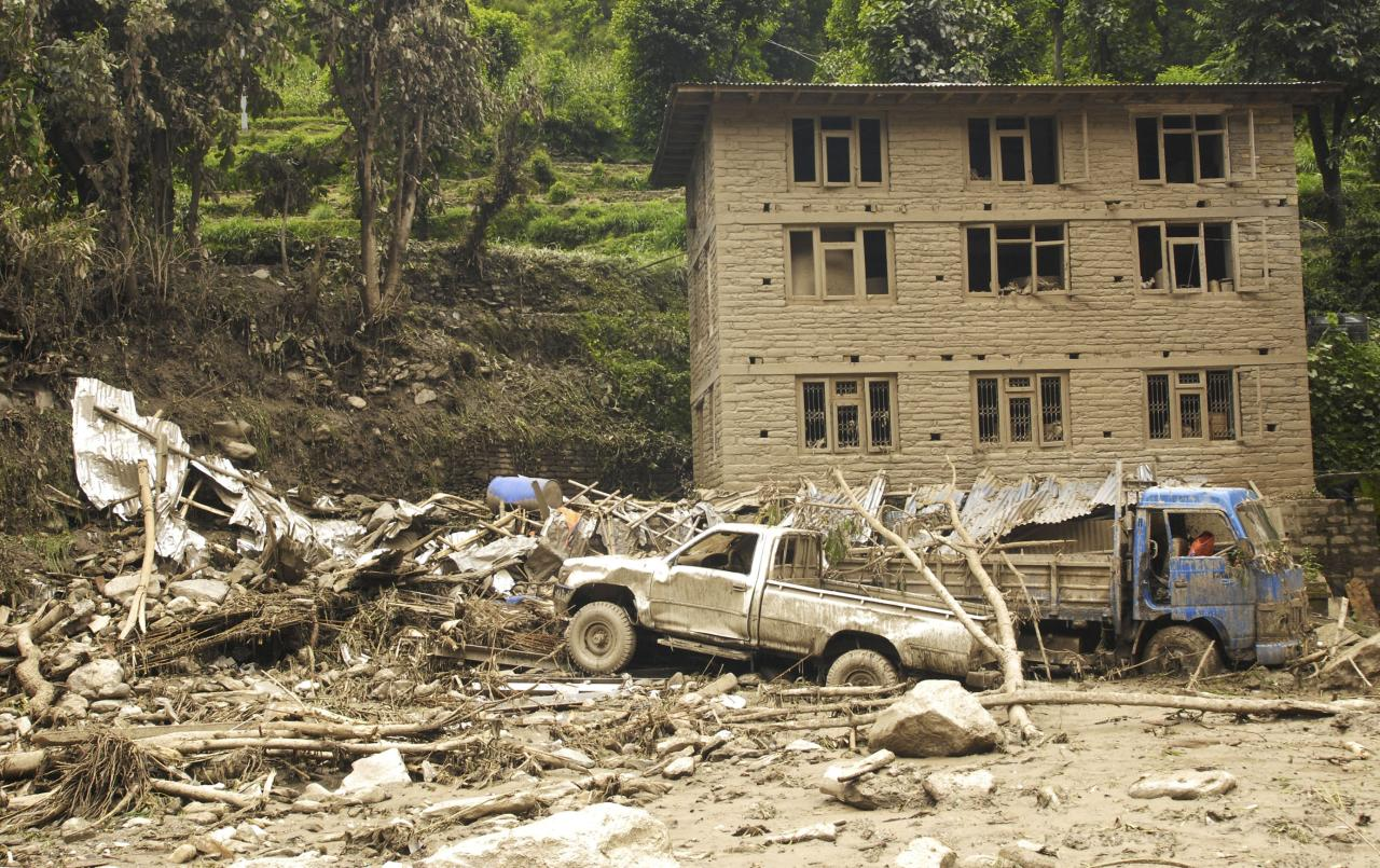 Damaged vehicles lie among the debris after a massive landslide in village Mankha, about 120 kilometers (75 miles) east of Katmandu, Nepal, Sunday, Aug.3, 2014. Nepalese officials say there is no chance of finding any of the more than 150 people, who are believed to have been buried by the early Saturday landslide in northern Nepal. (AP Photo/Arpan Shrestha)