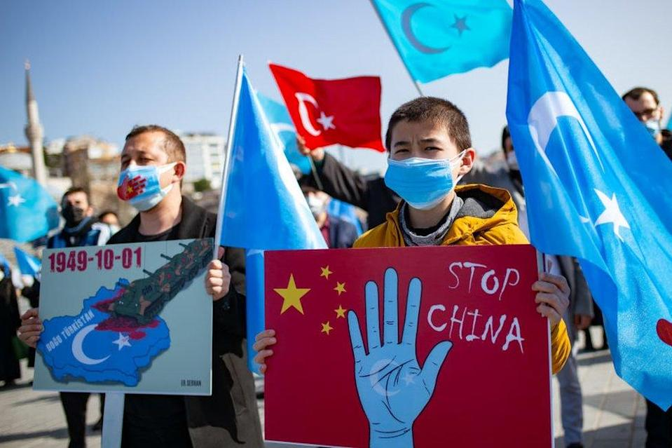 Members of the Muslim Uighur minority hold placards as they demonstrate to ask for news of their relatives and to express their concern about the ratification of an extradition treaty between China and Turkey at Uskudar square in Istanbul on February 26, 2021.